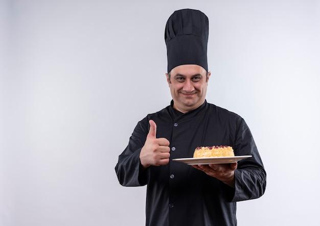 Erfreulicher männlicher koch mittleren alters in kochuniform, die kuchen auf teller hält, daumen auf isolierter weißer wand mit kopienraum