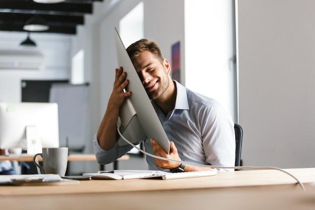 Erfreulicher männlicher manager, der spaß mit computer hat