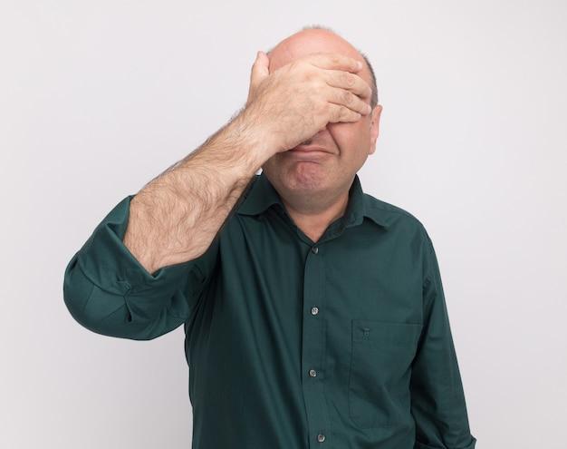 Erfreulicher mann mittleren alters, der grünes t-shirt bedecktes gesicht mit hand lokalisiert auf weißer wand trägt