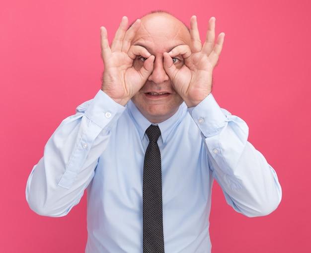 Erfreulicher mann mittleren alters, der weißes t-shirt mit krawatte trägt, die blickgeste lokalisiert auf rosa wand zeigt