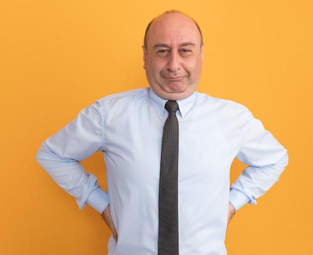 Erfreulicher mann mittleren alters, der weißes t-shirt mit krawatte trägt, die hände auf taille lokalisiert auf orange wand setzt