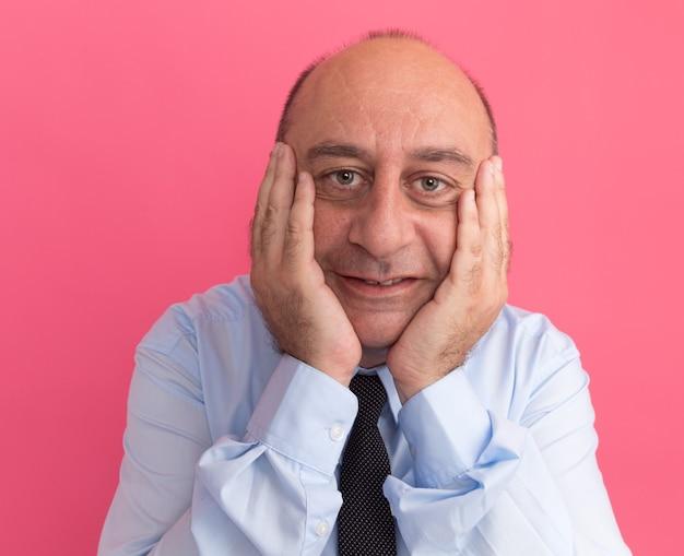 Erfreulicher mann mittleren alters, der weißes t-shirt mit krawatte trägt hände auf wangen isoliert auf rosa wand