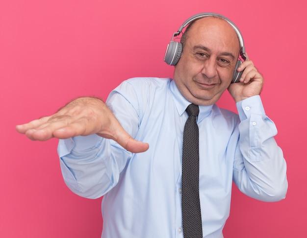 Erfreulicher mann mittleren alters, der weißes t-shirt mit krawatte und kopfhörern trägt, die hand lokalisiert auf rosa wand halten