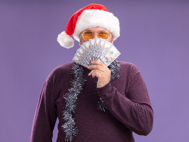 Erfreulicher mann mittleren alters mit weihnachtsmütze und lametta-girlande um den hals mit brille, die geld von hinten hält, isoliert auf lila wand