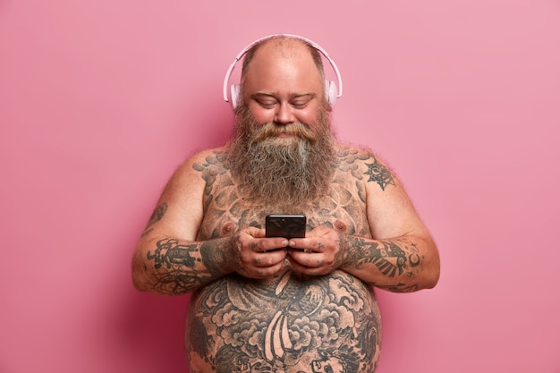 Erfreulicher praller mann mit nacktem tätowiertem körper, dickem bauch, hört musik in kopfhörern, hält handy, lädt lieder in wiedergabeliste herunter, isoliert auf rosa wand. menschen, übergewicht, hobby-konzept