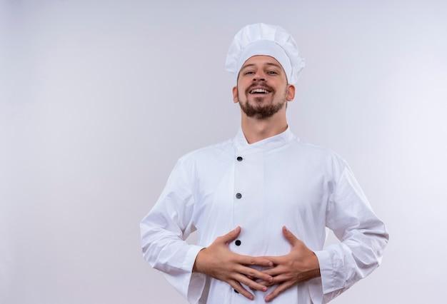 Erfreulicher professioneller männlicher kochkoch in der weißen uniform und im kochhut, der seine hände auf seinem bauch hält, der über weißem hintergrund steht