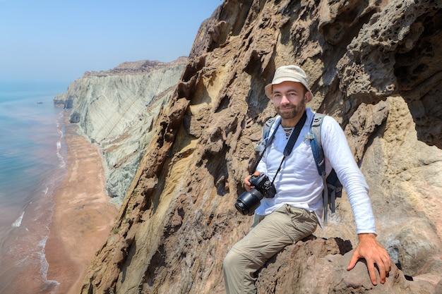 Erfreulicher reisender mit kamera sitzt am rand der klippe, hormuz island, hormozgan, iran.