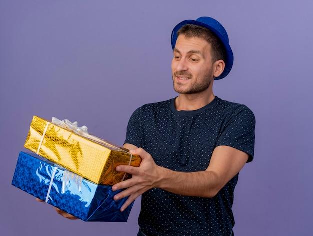 Erfreulicher schöner kaukasischer mann, der blauen hut trägt, hält und betrachtet geschenkboxen lokalisiert auf lila hintergrund mit kopienraum