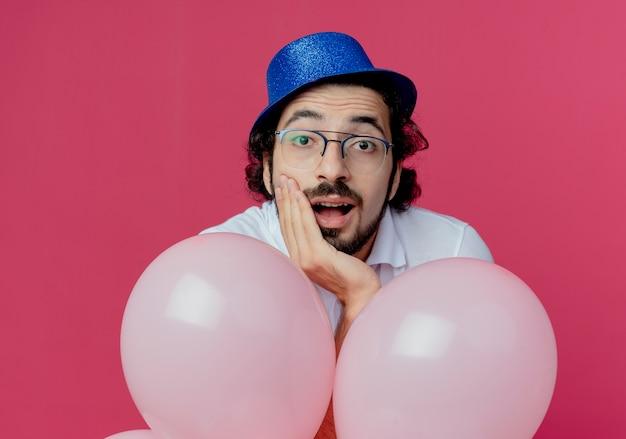 Erfreulicher schöner mann, der brille und blauen hut trägt, der ballons hält und hand auf kinn lokalisiert auf rosa hintergrund setzt