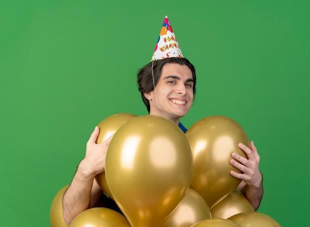 Erfreulicher schöner mann, der geburtstagskappe hält, hält heliumballons lokalisiert auf grüner wand
