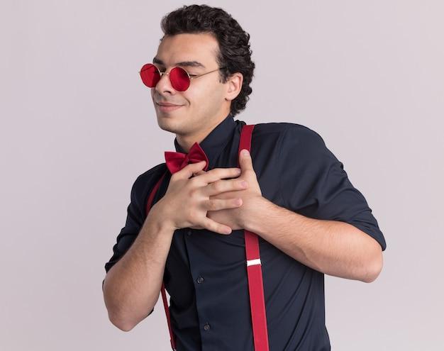 Erfreulicher stilvoller mann mit fliege, der brille und hosenträger mit gekreuzten händen auf der brust trägt und dankbar lächelt, über weißer wand stehend