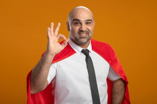 Erfreulicher superheld-geschäftsmann im roten umhang, der vorne lächelnd breit zeigt, ok zeichen zeigend, das über orange wand steht
