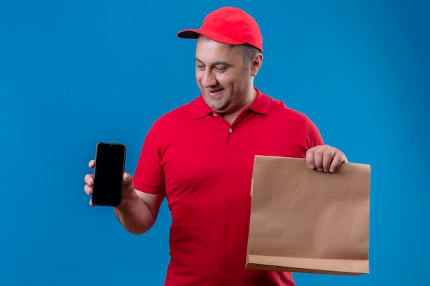 Erfreulicher zusteller, der rote uniform und kappe hält, die papierpaket hält, das handy mit glücklichem gesicht lächelnd über blauem hintergrund zeigt