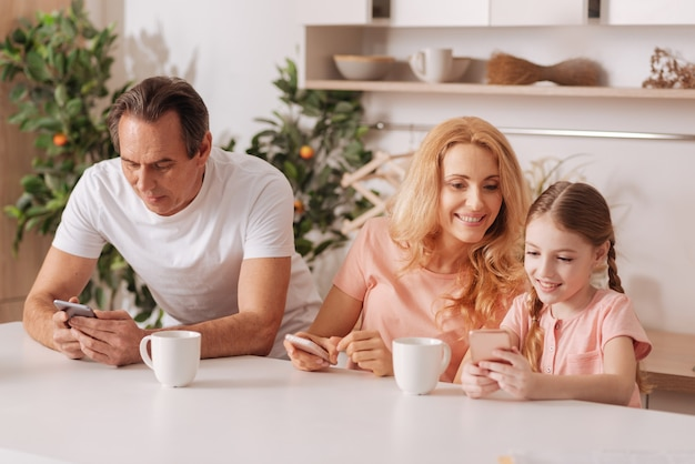 Erfreut amüsierte glückliche familie, die das wochenende zu hause genießt und sich ausruht, während sie elektronische geräte benutzt