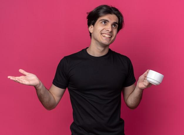 Erfreut an der seite junger, gutaussehender kerl mit schwarzem t-shirt, der eine tasse kaffee hält und die hand isoliert auf rosa wand ausbreitet