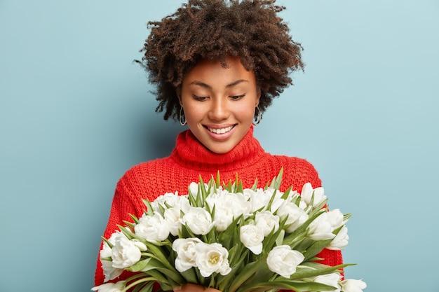 Erfreut angenehm aussehendes weibliches modell mit lockigem haar, sieht glücklich auf weißen frühlingsblumen aus