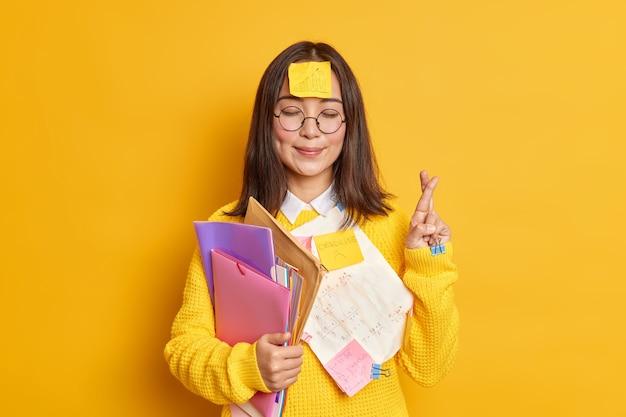 Erfreut asain studentin glaubt an viel glück bei prüfungsständen mit geschlossenen augen und daumen drücken glaubt, träume werden wahr, stecken mit papieren hält ordner.