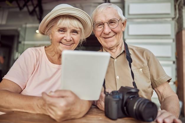 Erfreut attraktive ältere frau und ihr grauhaariger ehepartner mit brille, die an einem holztisch sitzen