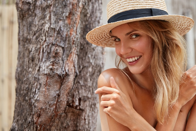 Erfreut attraktives weibliches model mit gesunder reiner haut, posiert nackt, versteckt ihren perfekten körper mit den händen, trägt nur sommerstrohhut. positive entzückende junge frau zeigt natürliche schönheit