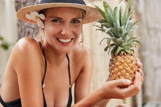 Erfreut attraktives weibliches model ruht in exotischem land, isst ananas, hat gebräunte haut, trägt badebekleidung, hat unvergessliche reise. schöne junge frau nimmt ein sonnenbad und genießt tropische früchte