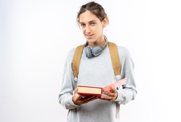Erfreut aussehende kamera junger kerl student mit rucksack mit kopfhörern am hals hält bücher