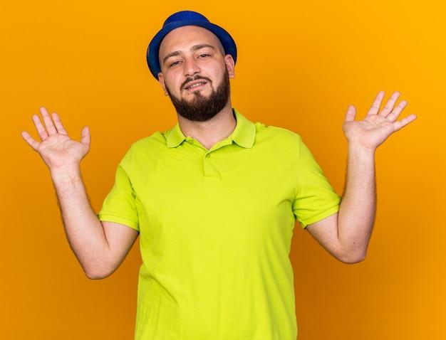 Erfreut aussehende kamera junger mann mit partyhut, der hände ausbreitet