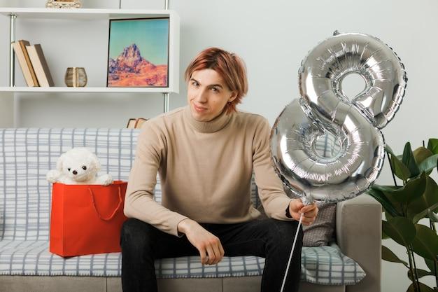 Erfreut aussehender gutaussehender kerl am glücklichen frauentag, der den ballon nummer acht hält, der auf dem sofa im wohnzimmer sitzt