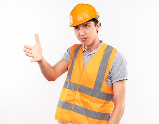 Erfreut aussehender junger baumeister in uniform, der die hand an der seite ausstreckt