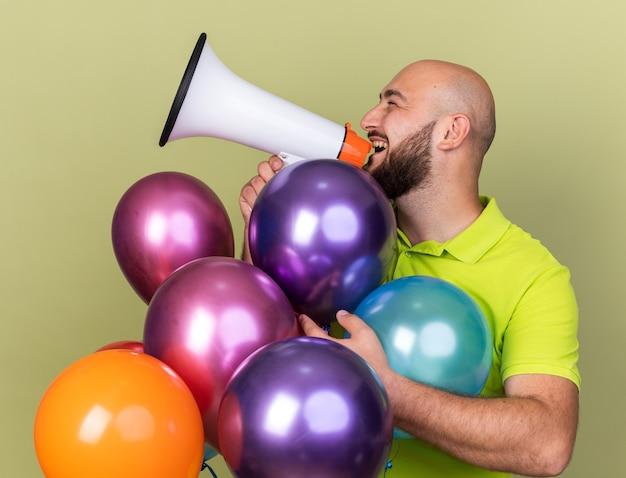 Erfreut aussehender junger mann mit gelbem t-shirt, der hinter ballons steht, spricht über lautsprecher