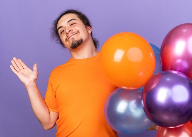 Erfreut aussehender junger mann mit kamera, der die hand ausbreitet, die in der nähe von luftballons steht, isoliert auf lila wand