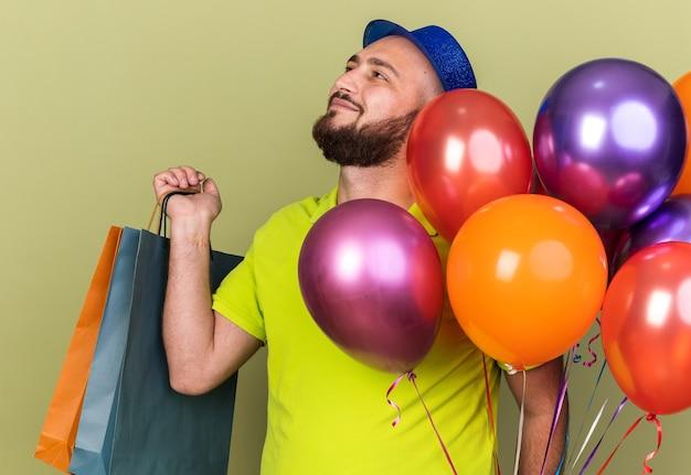 Erfreut aussehender junger mann mit partyhut, der geschenktüten isoliert auf olivgrüner wand hält