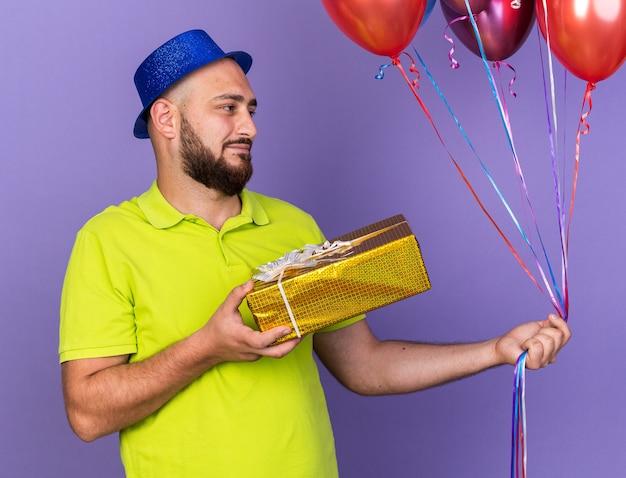 Erfreut aussehender junger mann mit partyhut, der luftballons mit geschenkbox hält