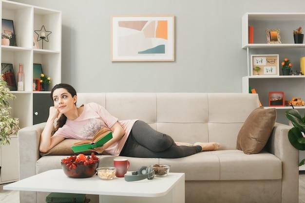 Erfreut aussehendes junges mädchen, das auf dem sofa hinter dem couchtisch liegt und ein buch im wohnzimmer hält?