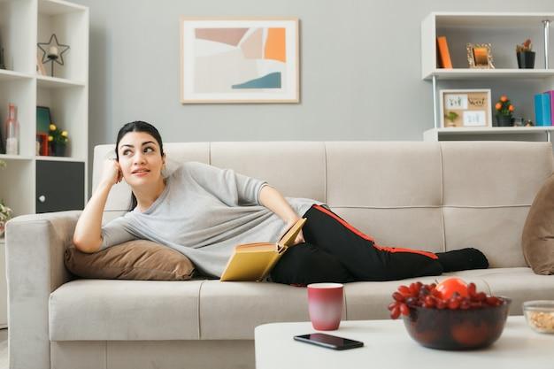 Erfreut aussehendes junges mädchen, das ein buch auf dem sofa hinter dem couchtisch im wohnzimmer hält