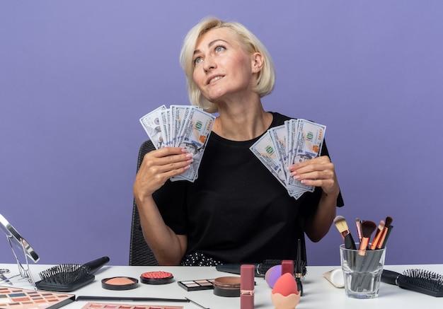 Erfreut blick auf den seitlich geneigten kopf junges schönes mädchen sitzt am tisch mit make-up-tools, die bargeld isoliert auf blauer wand halten holding