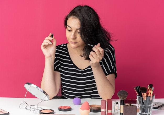 Erfreut blick auf den spiegel junges schönes mädchen sitzt am tisch mit make-up-tools, die eyeliner isoliert auf rosa wand halten