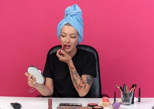 Erfreut blick auf den spiegel junges schönes mädchen sitzt am tisch mit make-up-tools, die haare in ein handtuch gewickelt haben und lippenstift auf rosa wand auftragen