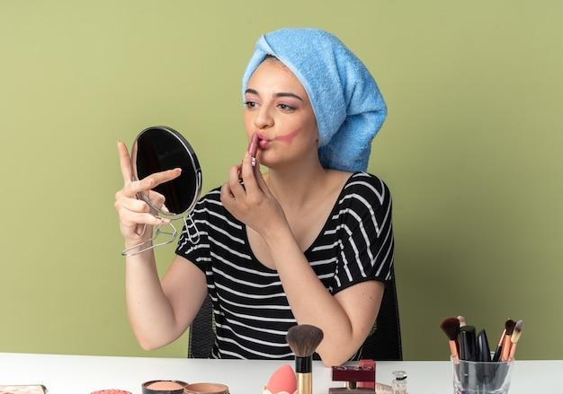 Erfreut blick auf den spiegel junges schönes mädchen sitzt am tisch mit make-up-tools, die haare in ein handtuch gewickelt haben und lippenstift einzeln auf olivgrüner wand auftragen
