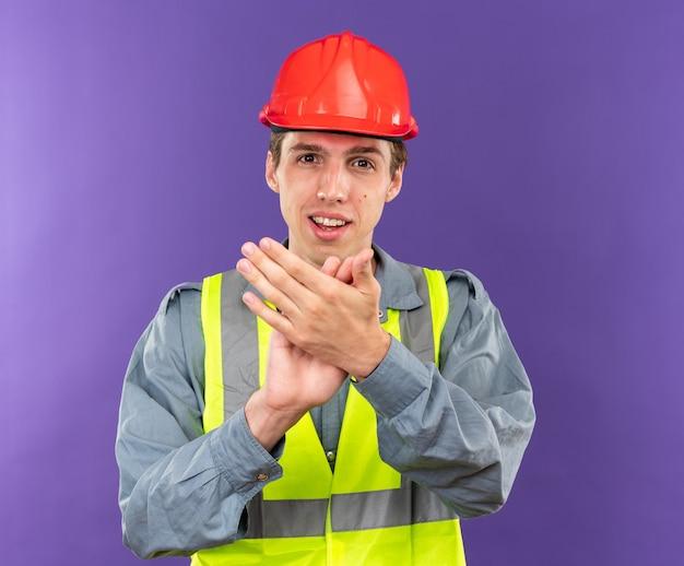 Erfreut blick in die kamera junger baumeister in uniform mit handschlag-geste