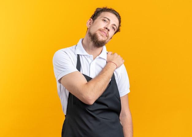 Erfreut, den kopf des jungen männlichen friseurs in uniform zu kippen, der die hand auf die schulter legt, isoliert auf gelber wand