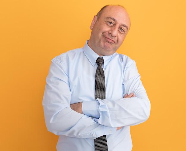 Erfreut, den kopf eines mannes mittleren alters zu neigen, der ein weißes t-shirt mit krawattenkreuzenden händen trägt, die auf einer orangefarbenen wand isoliert sind?