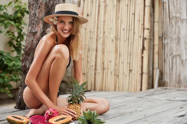 Erfreut entzückendes weibliches model trägt schwarzen bikini, sommerhut, sitzt auf holzboden mit exotischen früchten,