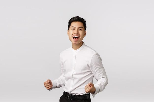 Erfreut, erfolgreicher junger asiatischer geschäftsmann ballt die fäuste, pumpt sie auf und lächelt erfreut, sagt ja, feiert den sieg, platziert ein gutes gebot, erreicht das ziel, freut sich, erhält den preis,