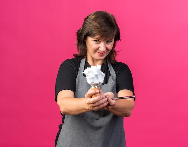 Erfreut erwachsene kaukasische friseurin in uniform mit rasiermesser und rasierpinsel mit schaum oben einzeln auf rosafarbenem hintergrund mit kopierraum