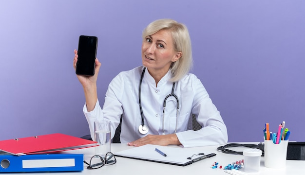 Erfreut erwachsene slawische ärztin in medizinischer robe mit stethoskop am schreibtisch sitzend mit bürowerkzeugen, die telefon auf violettem hintergrund mit kopienraum isoliert halten holding
