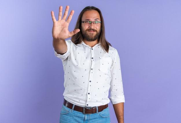 Erfreut erwachsener, gutaussehender mann mit brille, der auf die kamera blickt, die fünf mit der hand zeigt, die auf lila wand mit kopierraum isoliert ist?