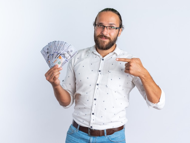 Erfreut erwachsener gutaussehender mann mit brille, der auf geld zeigt und zeigt