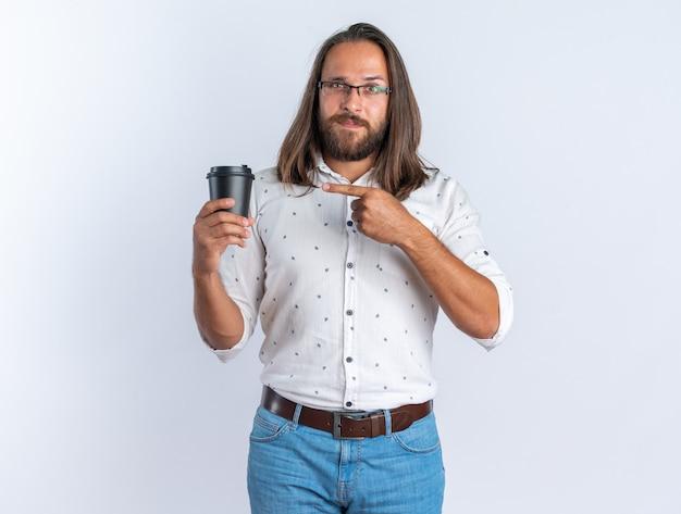 Erfreut erwachsener gutaussehender mann mit brille, der auf plastikkaffeetasse hält und zeigt