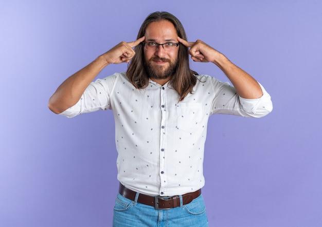 Erfreut erwachsener, gutaussehender mann mit brille, der die kamera anschaut und eine denkgeste macht, die auf lila wand isoliert ist?