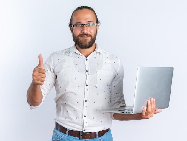Erfreut erwachsener gutaussehender mann mit brille, der laptop mit daumen nach oben hält